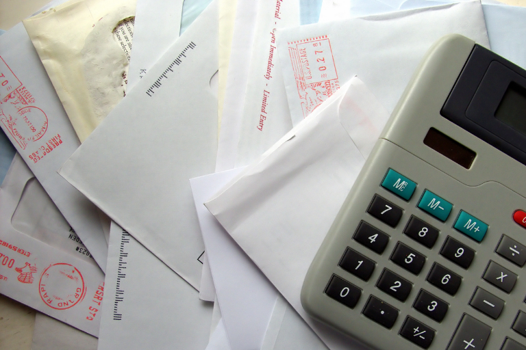 Image of a pile of bills received in the mail and a calculator.